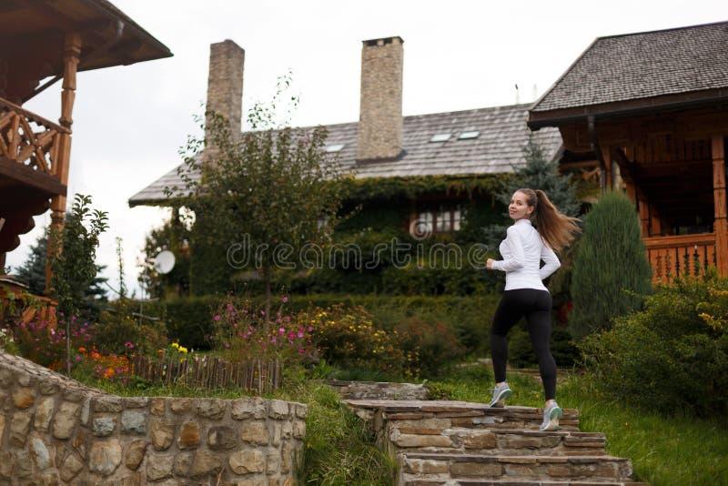 Donna sportiva esile che corre di sopra Bella ragazza sulla traccia di addestramento in ghette e scarpe da tennis Case di legno s fotografia stock