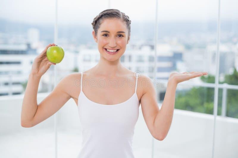 Donna sportiva felice che tiene mela verde immagine stock libera da diritti