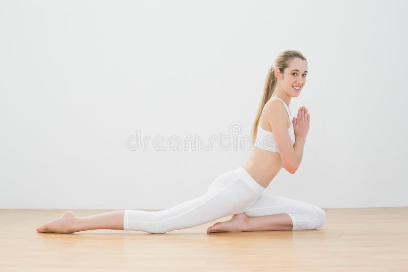 Donna sportiva giuliva che fa posa di yoga sul pavimento nella palestra immagine stock