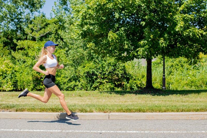 Donna sportiva nel funzionamento della traccia degli abiti sportivi sulla strada La ragazza dell'atleta sta pareggiando nel parco immagini stock libere da diritti