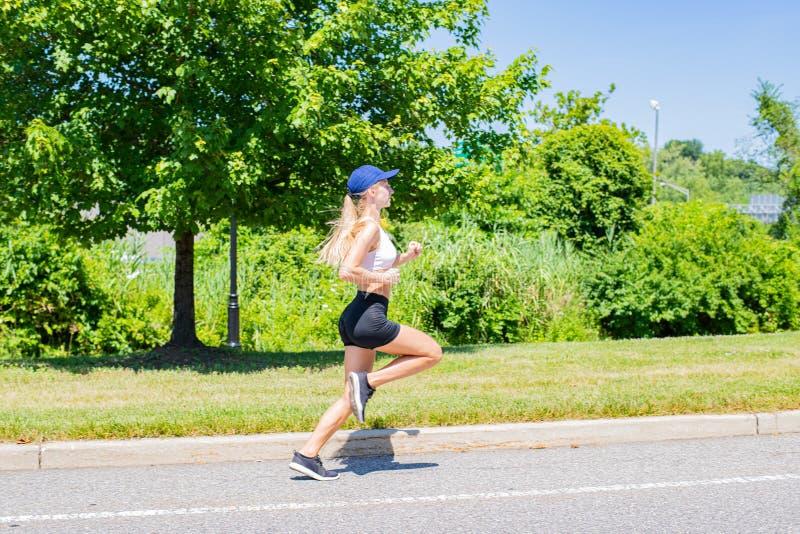 Donna sportiva nel funzionamento della traccia degli abiti sportivi sulla strada La ragazza dell'atleta sta pareggiando nel parco fotografie stock libere da diritti