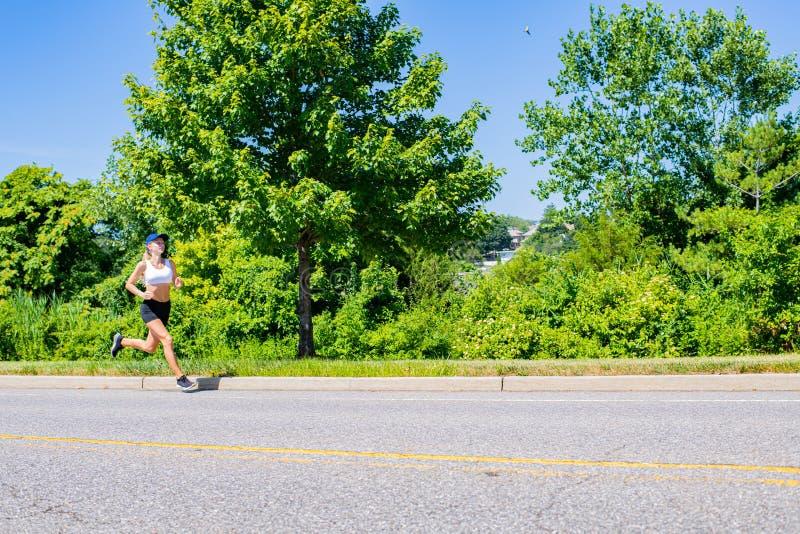 Donna sportiva nel funzionamento della traccia degli abiti sportivi sulla strada La ragazza dell'atleta sta pareggiando nel parco fotografia stock libera da diritti