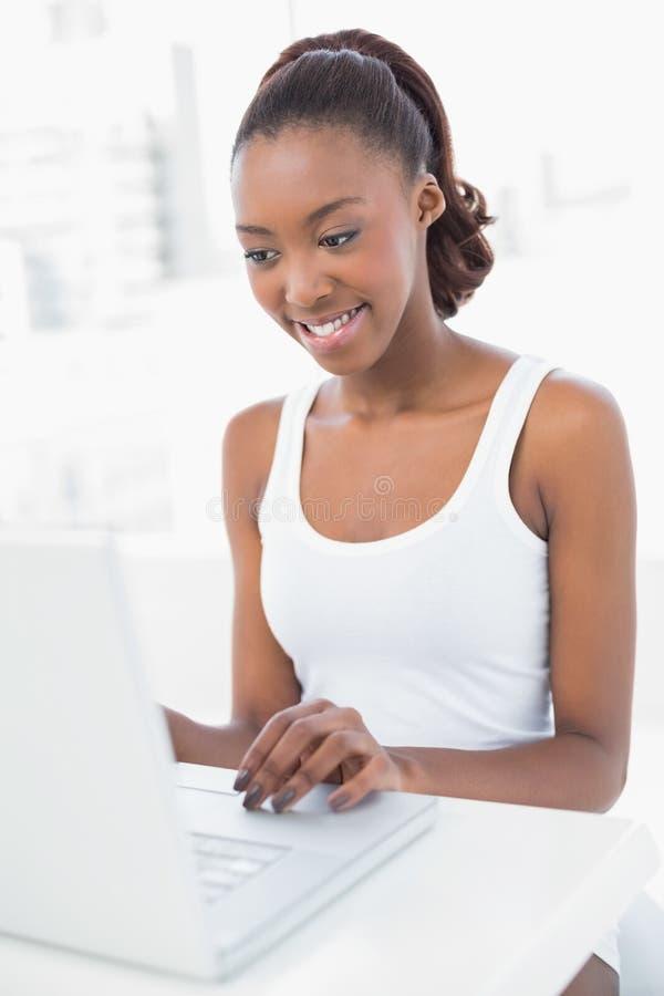 Donna sportiva pacifica che per mezzo del suo computer portatile fotografia stock