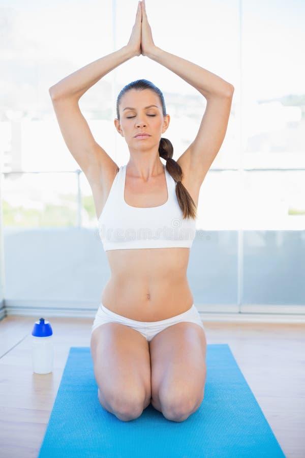 Donna sportiva pacifica che si siede nella posizione di yoga sulla stuoia di esercizio fotografie stock libere da diritti