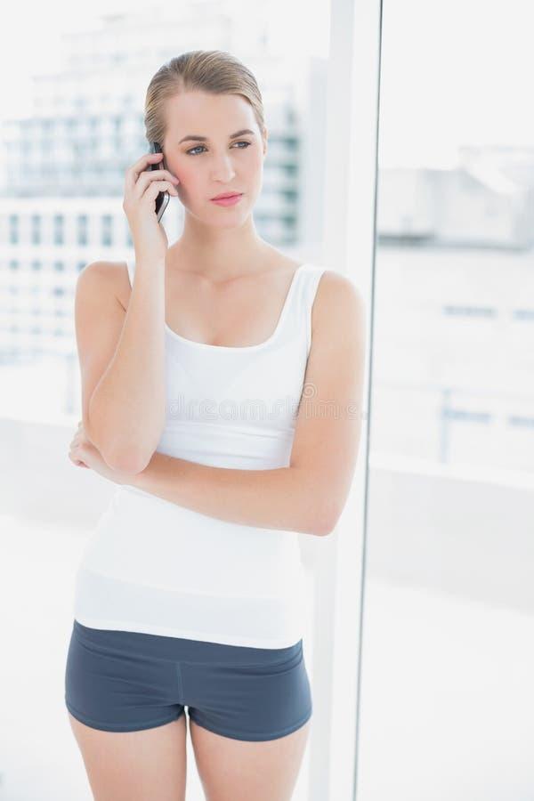 Donna sportiva pensierosa sul telefono fotografie stock