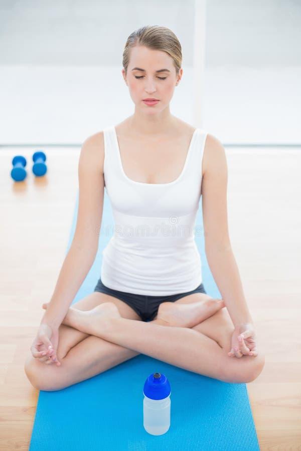 Donna sportiva rilassata nella posa di posizione di loto fotografia stock