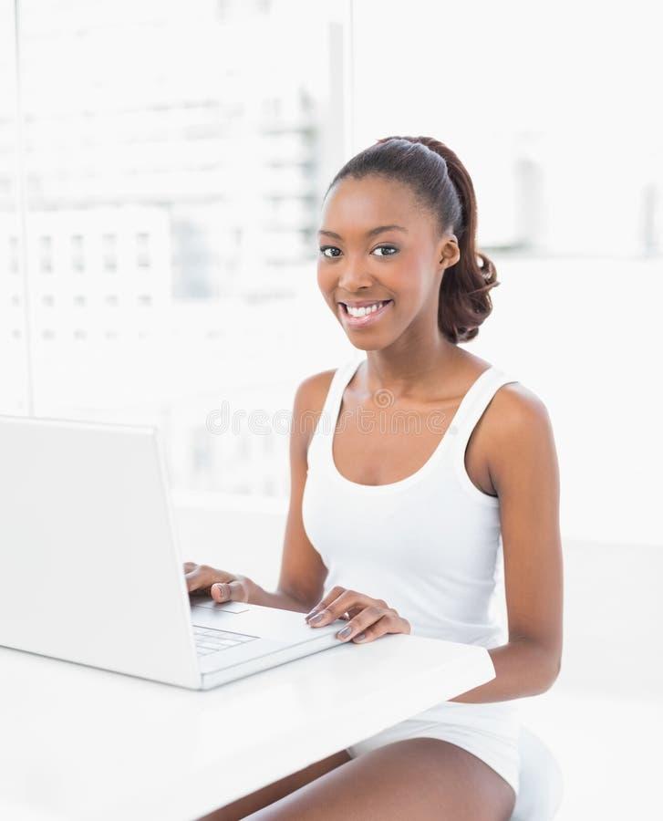 Donna sportiva sorridente che per mezzo del suo computer portatile fotografia stock libera da diritti