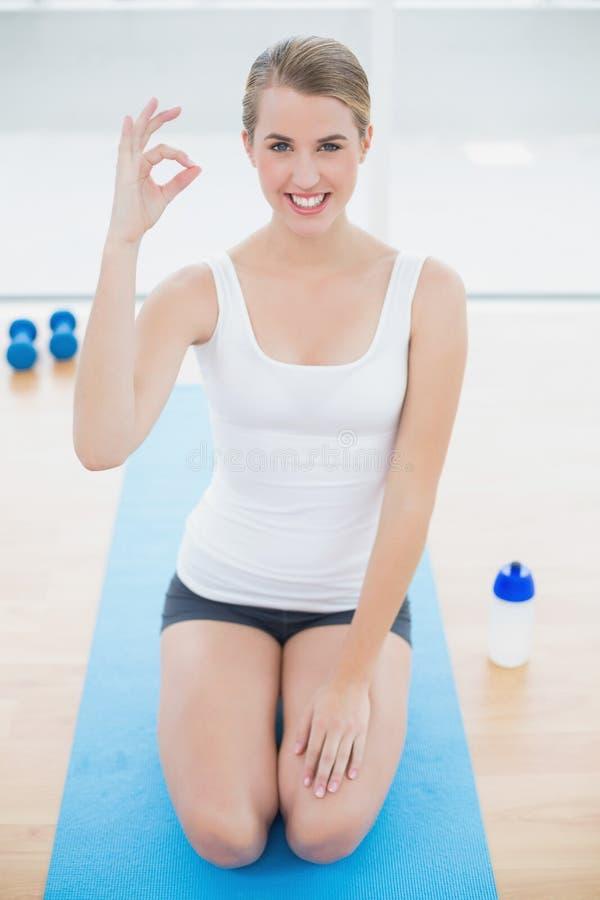 Donna sportiva sorridente sulle sue ginocchia che danno gesto giusto fotografia stock