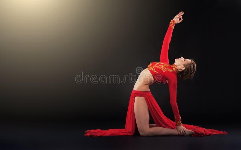 Donna sportiva splendida in abbigliamento rosso che fa esercizio di yoga fotografia stock libera da diritti
