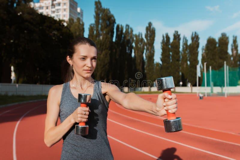 Donna sportiva splendida che fa gli esercizi con le teste di legno al fotografie stock libere da diritti