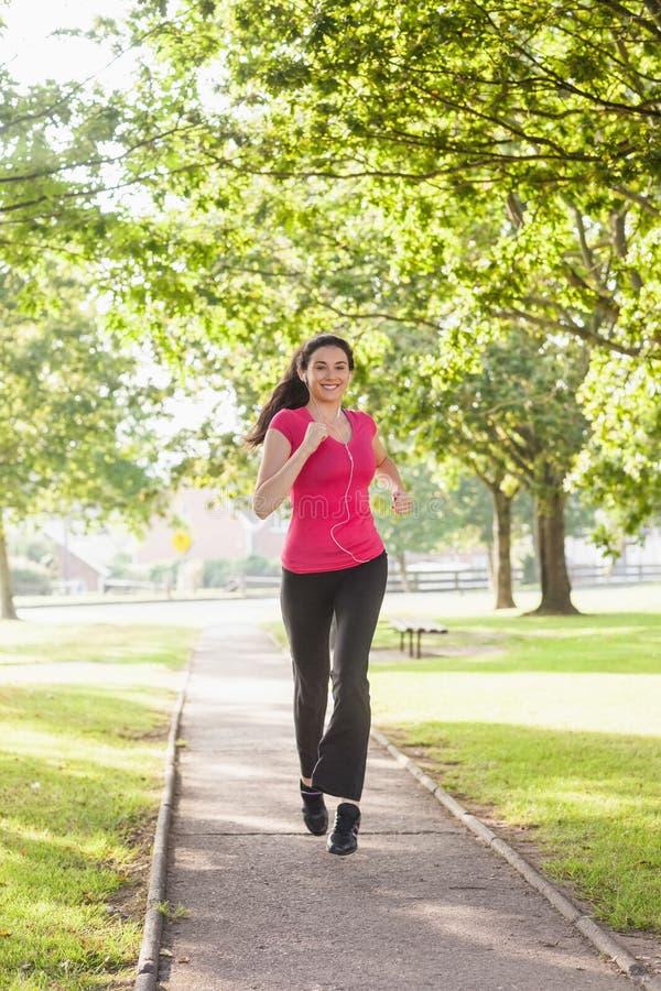 Donna sportiva splendida che pareggia in un parco fotografie stock