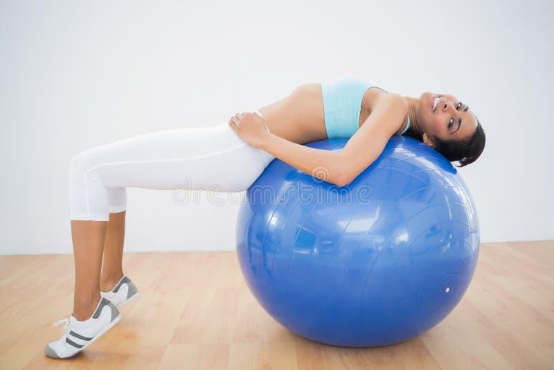 Donna sportiva sveglia che allunga sulla palla di forma fisica immagini stock