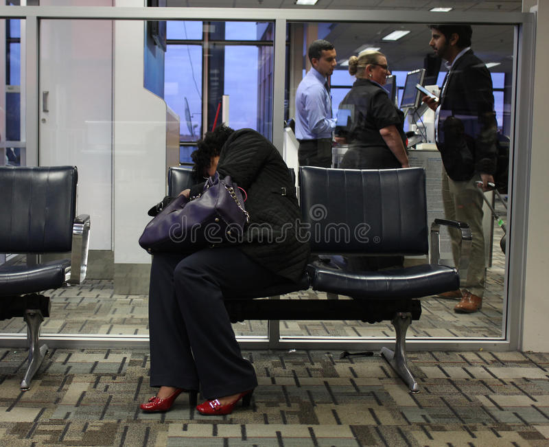 Donna stanca che dorme nell'aeroporto fotografia stock