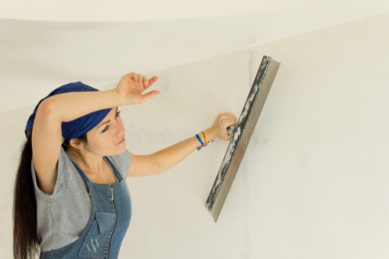 Donna stanca che wallpapering una parete immagine stock
