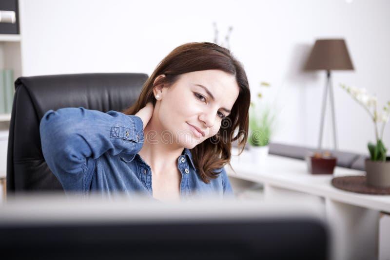 Donna stanca dell'ufficio che tiene indietro del suo collo fotografia stock libera da diritti