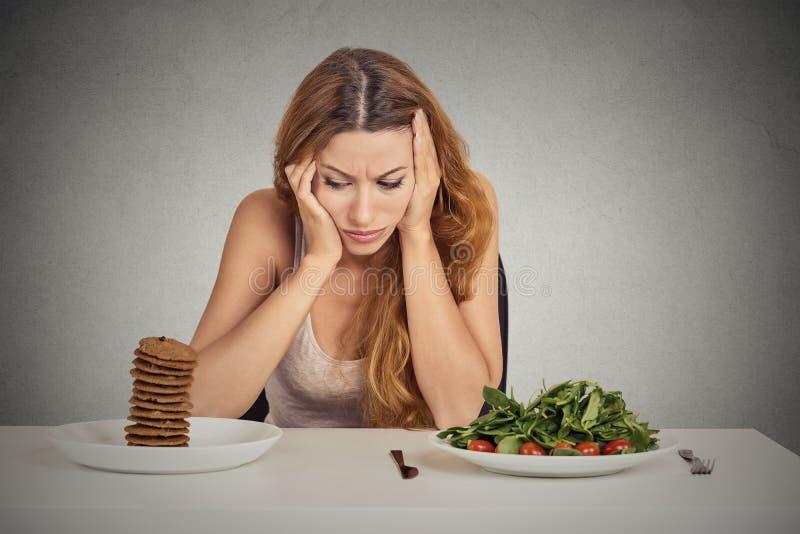 Donna stanca delle restrizioni di dieta che decidono di mangiare alimento sano o i biscotti dolci fotografia stock