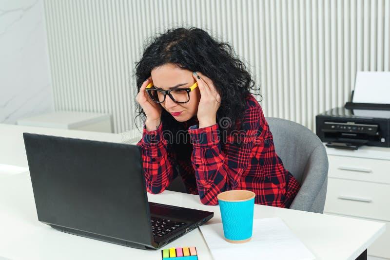Donna stanca di affari nel luogo di lavoro Donna sollecitata che lavora al computer portatile in ufficio moderno Mano della holdi fotografia stock libera da diritti