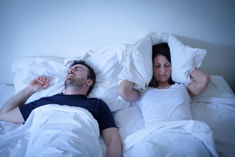Donna stanca ed infastidita del suo ragazzo che russa a letto immagini stock