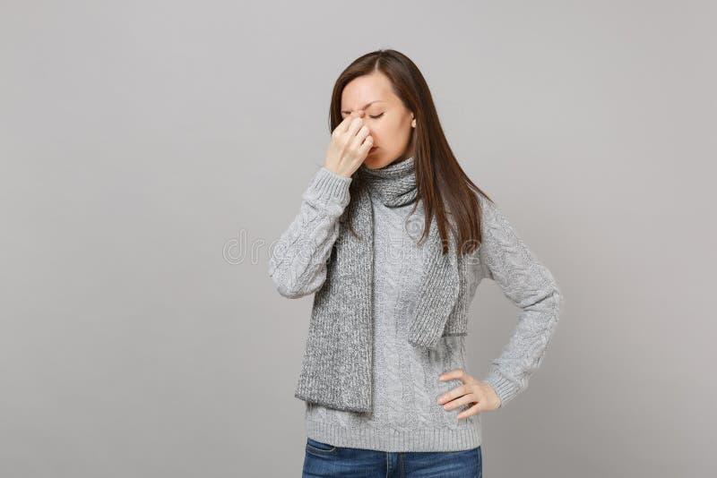 Donna stanca in maglione grigio, sciarpa che tiene gli occhi chiusi, mettendo mano sul fronte su fondo grigio Sano fotografia stock