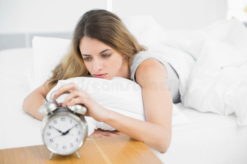 Donna stanca splendida che si trova sul suo letto fotografia stock