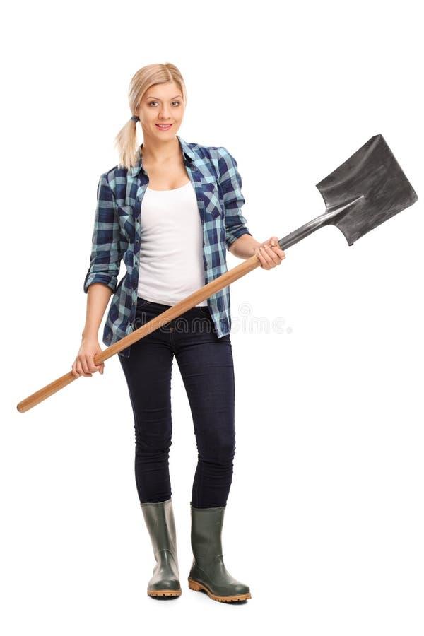 Donna in stivali di gomma grigi che tengono una pala immagini stock