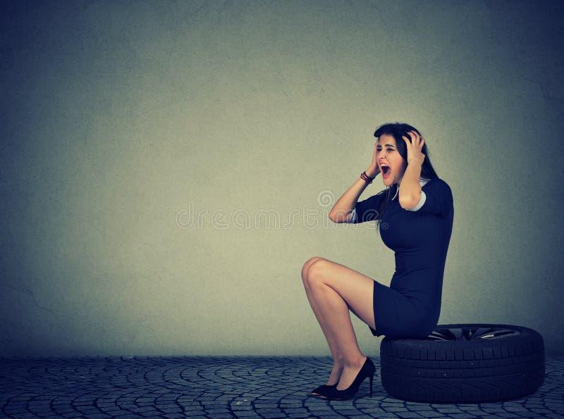Donna stressante che grida mentre sedendosi sulla gomma fotografia stock
