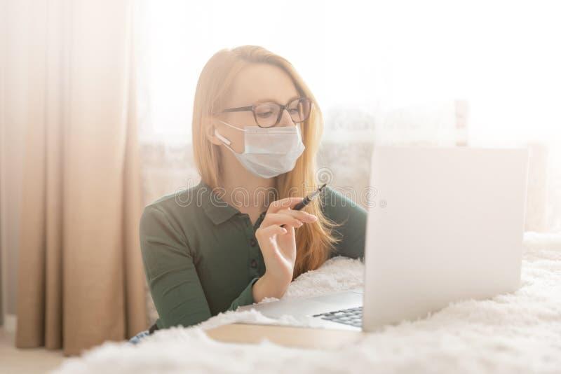 Donna studentessa freelancer che lavora online dietro il coronavirus della quarantena per computer portatili immagine stock