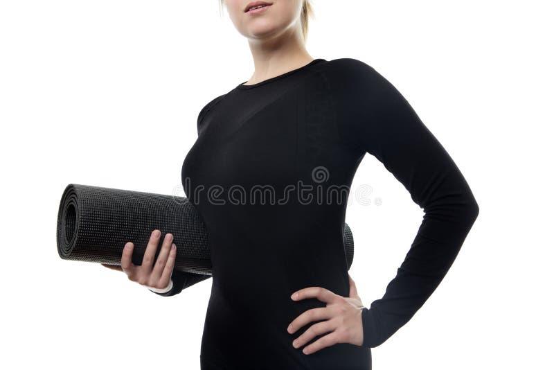 donna in stuoia nera di yoga della tenuta fotografia stock
