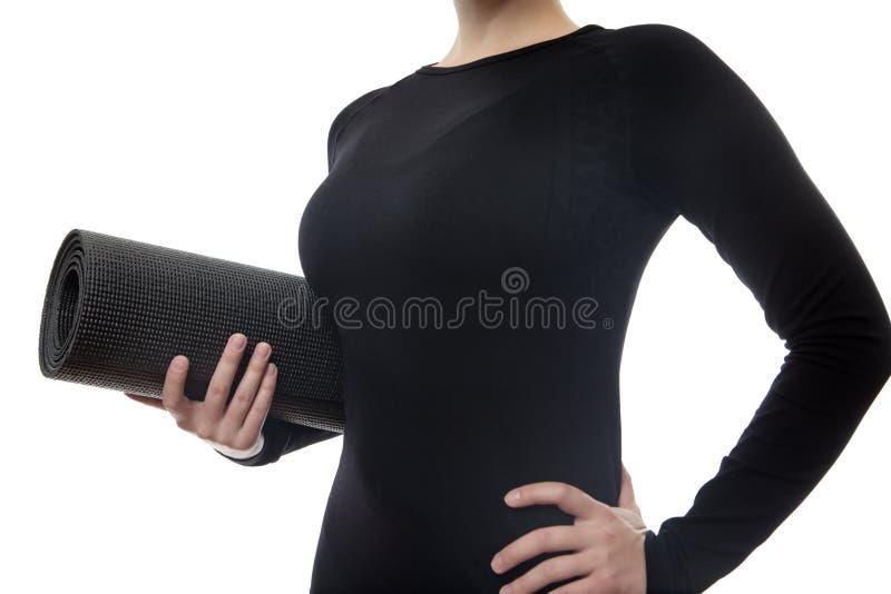 donna in stuoia nera di yoga della tenuta fotografia stock libera da diritti