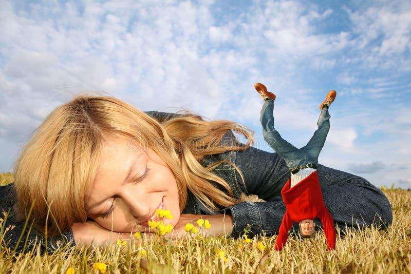 Donna su erba, ragazzo miniatura sulle mani immagine stock