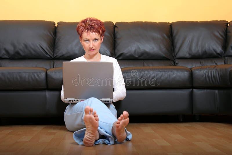 Donna su un computer portatile 3 immagini stock