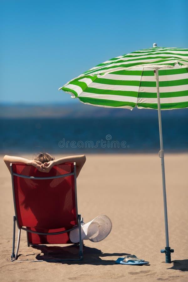 Donna su un deckchair alla spiaggia immagine stock