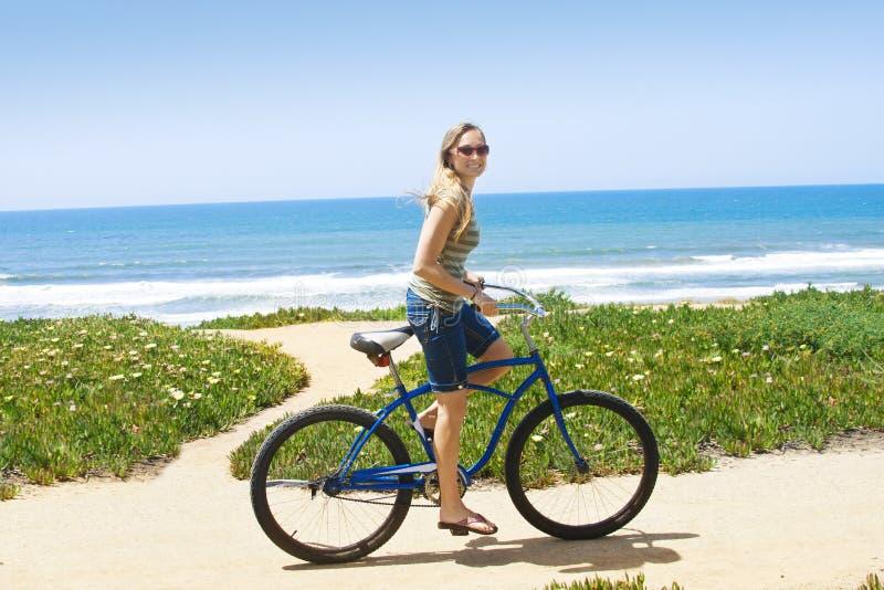 Donna su un giro della bicicletta lungo la spiaggia fotografia stock