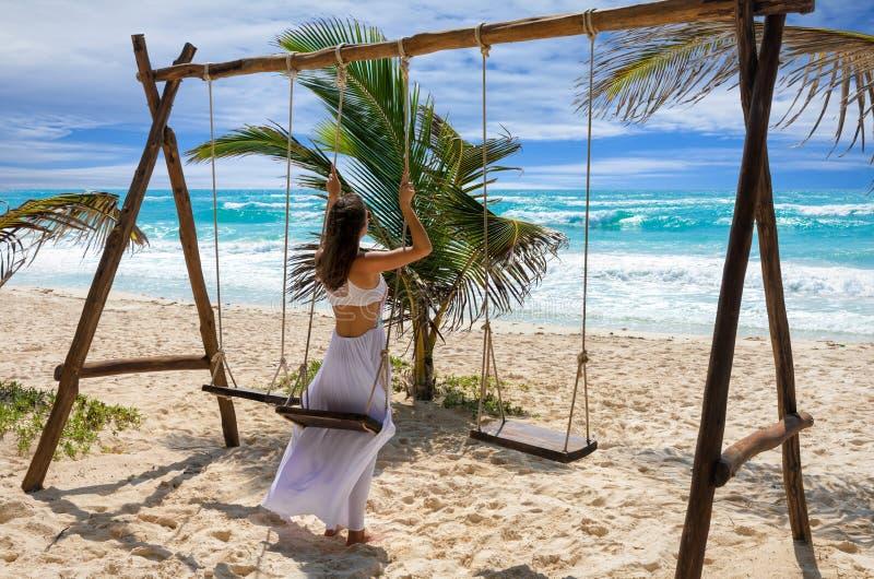 Donna su un'oscillazione ad una spiaggia caraibica, Tulum immagine stock