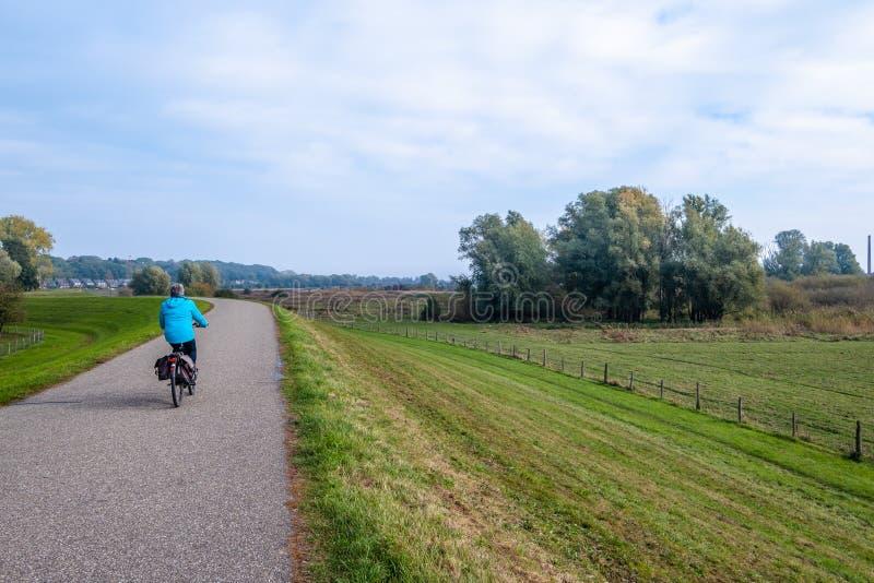 Donna su una bicicletta sulla diga lungo le pianure alluvionali lungo immagini stock