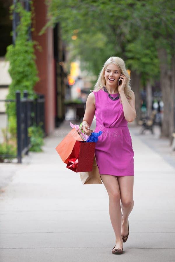 Donna su una chiamata mentre trasportando i sacchetti di acquisto fotografia stock