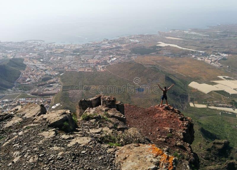 Donna su una cima di una montagna che gode della vista della valle immagini stock