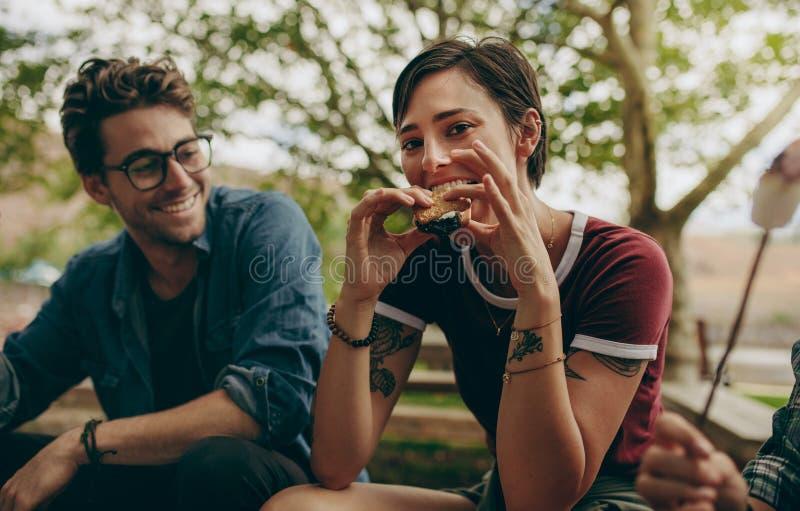 Donna su una festa che mangia il panino del biscotto che si siede all'aperto fotografie stock libere da diritti