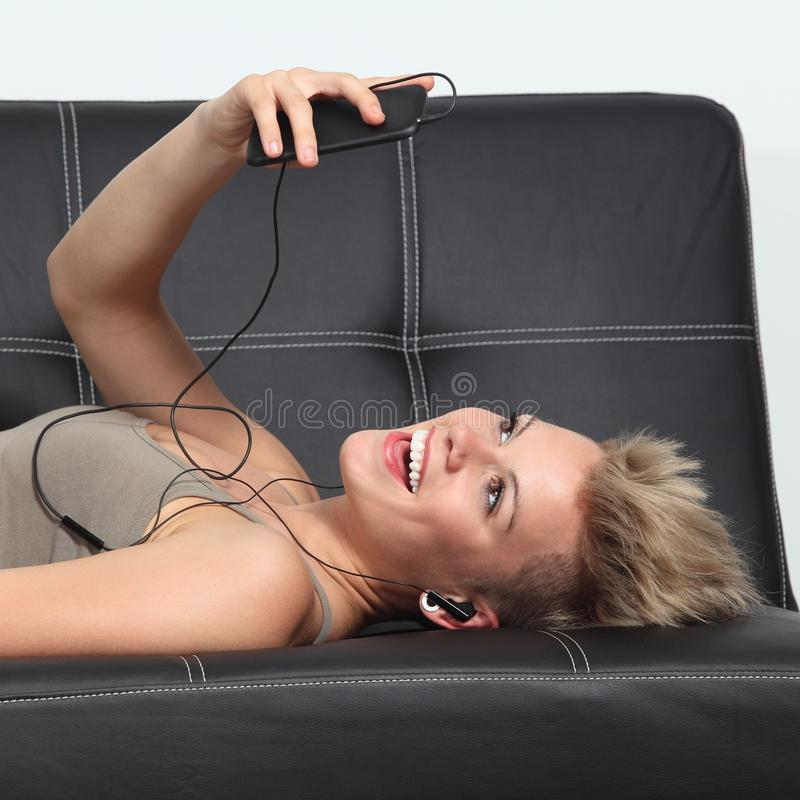Donna su uno strato a casa che ascolta la musica da uno smartphone fotografia stock libera da diritti