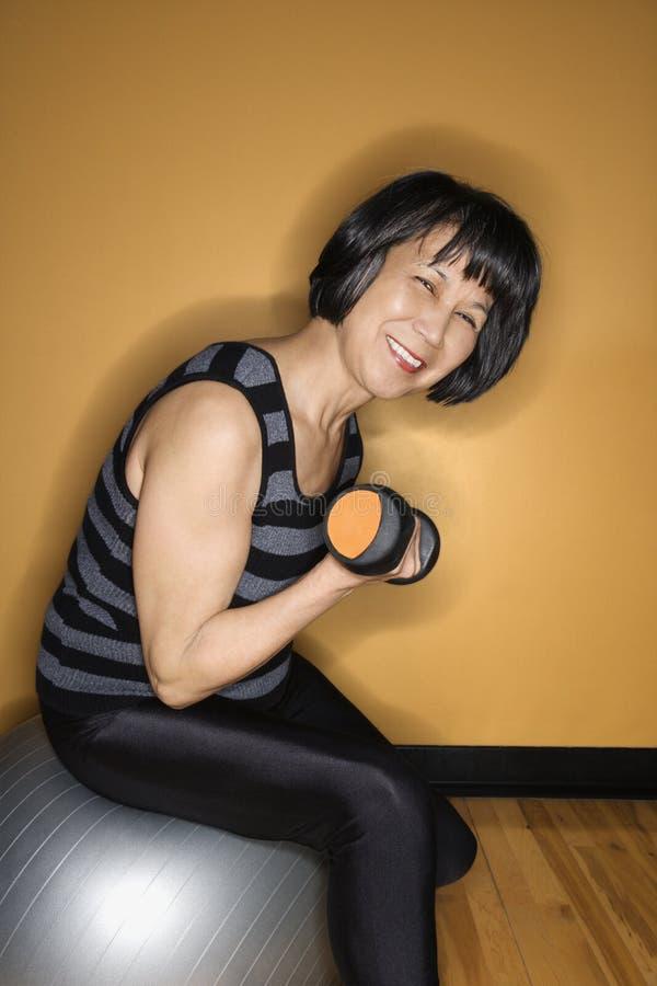 Donna sui pesi di sollevamento della sfera dell'equilibrio immagini stock libere da diritti