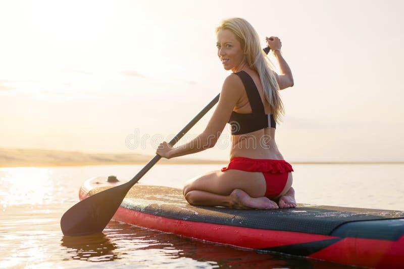 Donna sul bordo di pagaia al tramonto fotografie stock libere da diritti