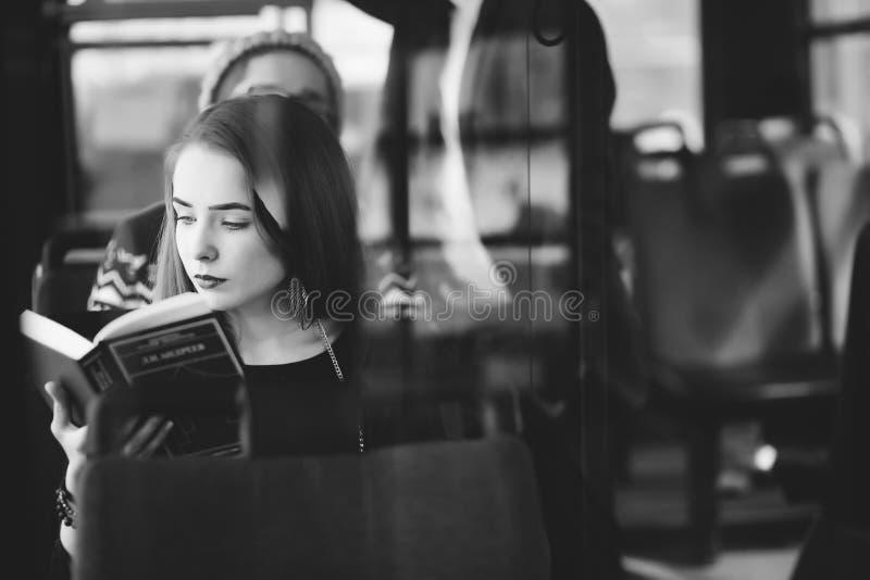 Donna sul bus che legge un libro fotografie stock