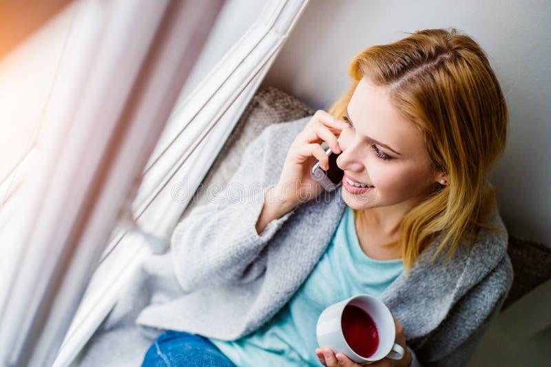 Donna sul davanzale della finestra con lo smartphone che fa telefonata fotografia stock libera da diritti