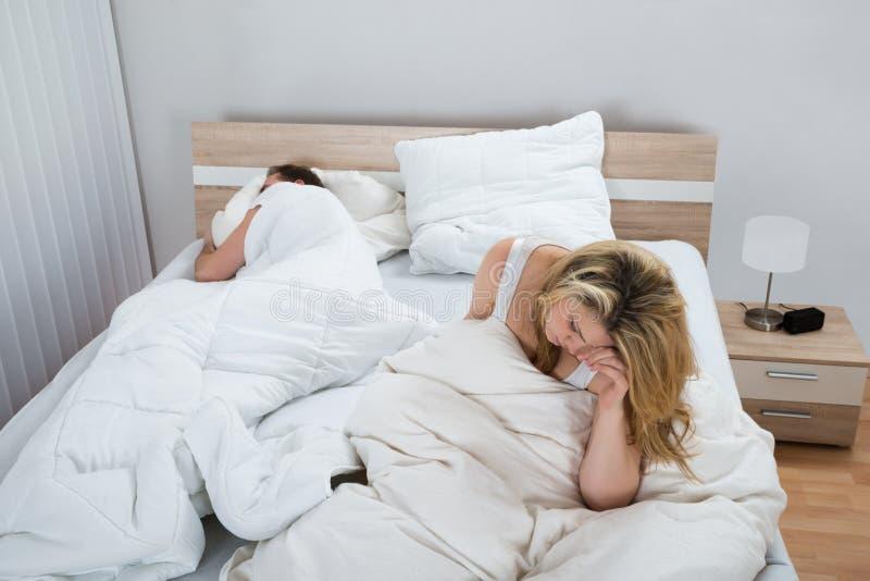 Download Donna Sul Letto Mentre Uomo Che Dorme Nella Camera Da Letto Fotografia Stock - Immagine di cuscino, frustrato: 55356728