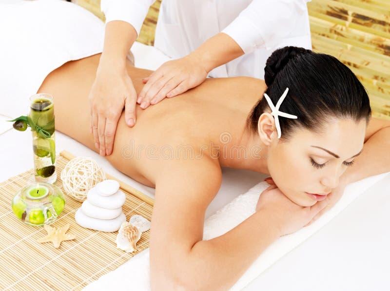 Donna sul massaggio di terapia della parte posteriore nel salone della stazione termale immagine stock