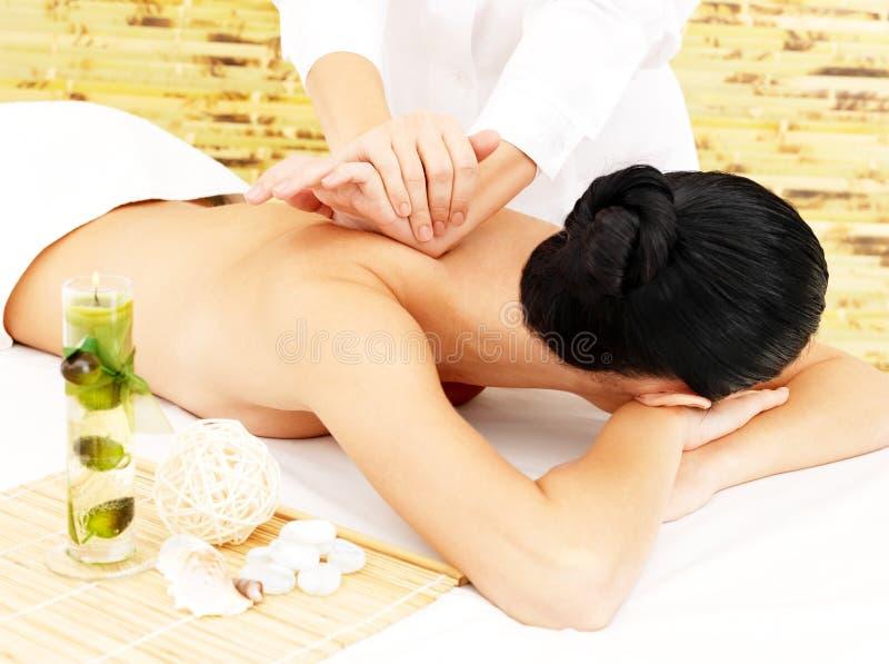 Donna sul massaggio di terapia della parte posteriore nel salone della stazione termale immagini stock libere da diritti