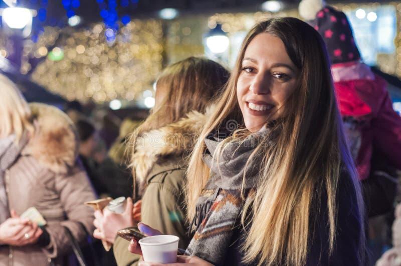 Donna sul mercato festivo di Natale alla notte Donna felice che ritiene la vibrazione urbana di natale alla notte immagine stock