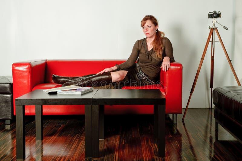 Donna sul sofà rosso immagine stock libera da diritti