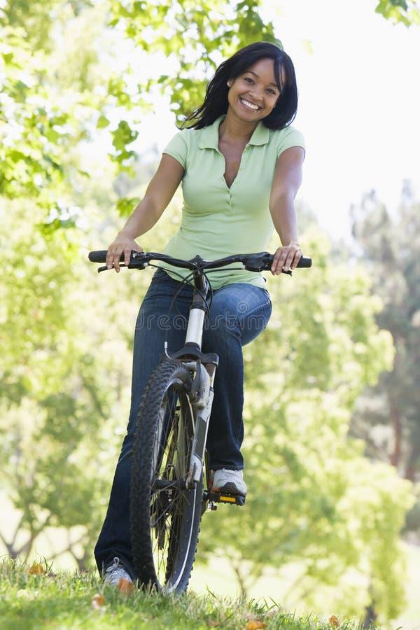 Donna sul sorridere della bicicletta fotografie stock libere da diritti