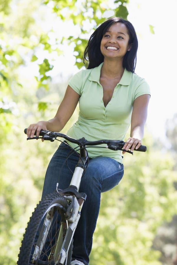 Donna sul sorridere della bicicletta fotografie stock
